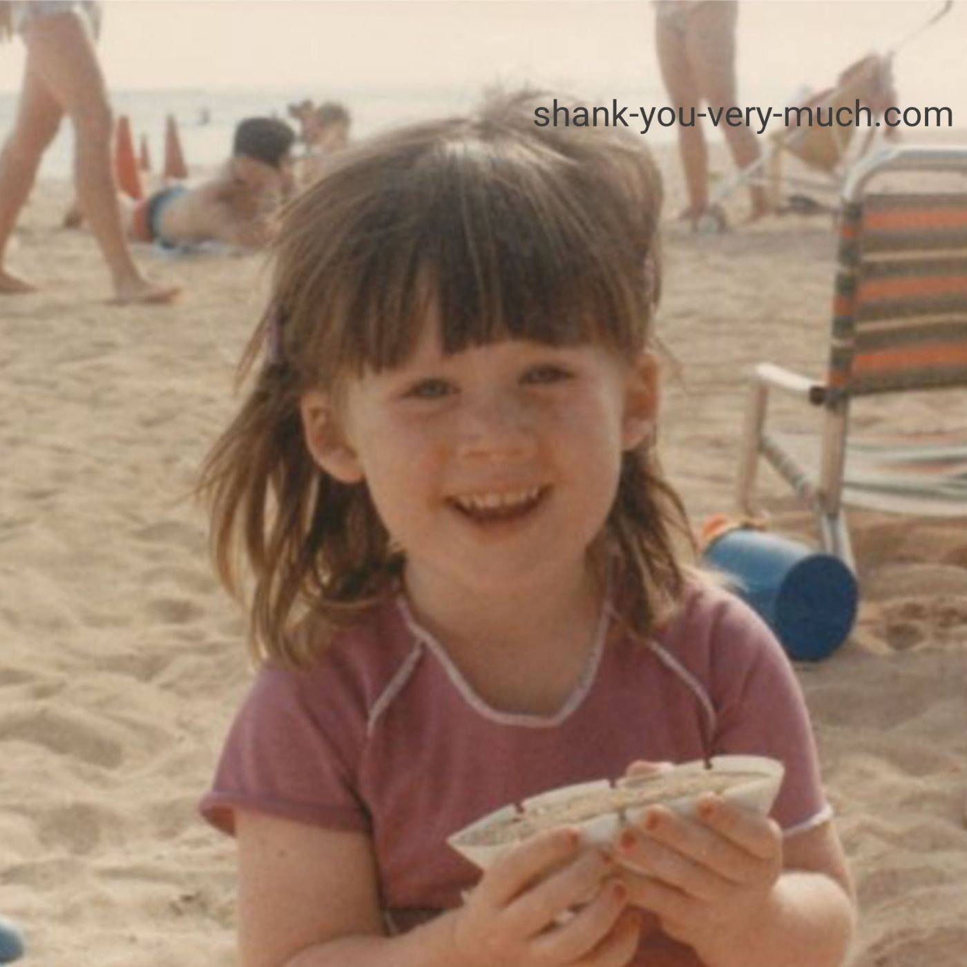 A photo of young Heather sitting on a sandy beach smiling.