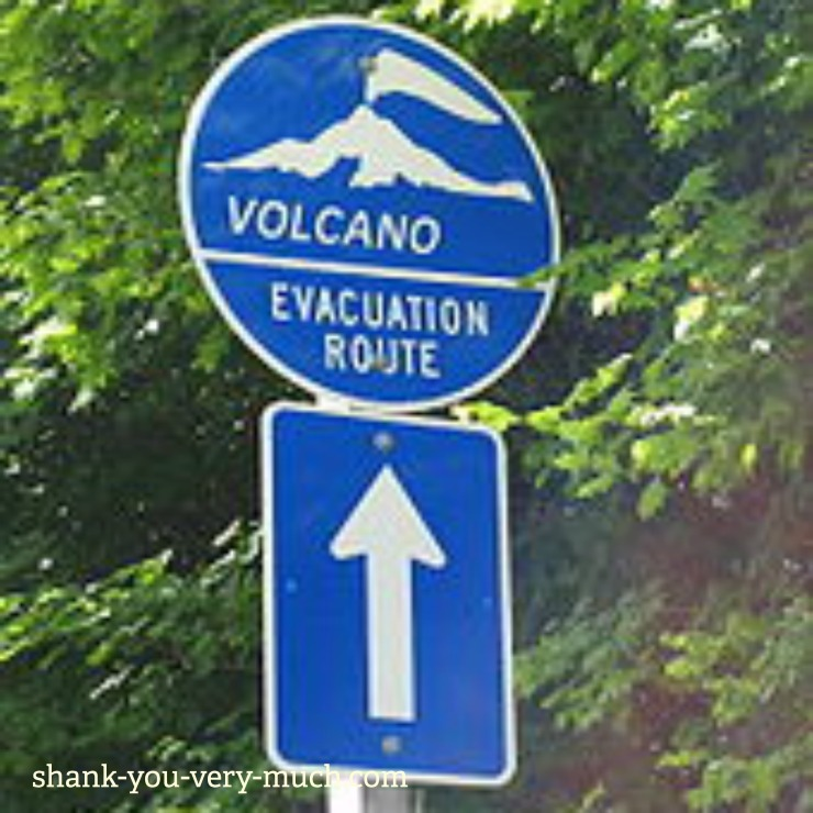 A volcano evacuation street sign with directional arrow