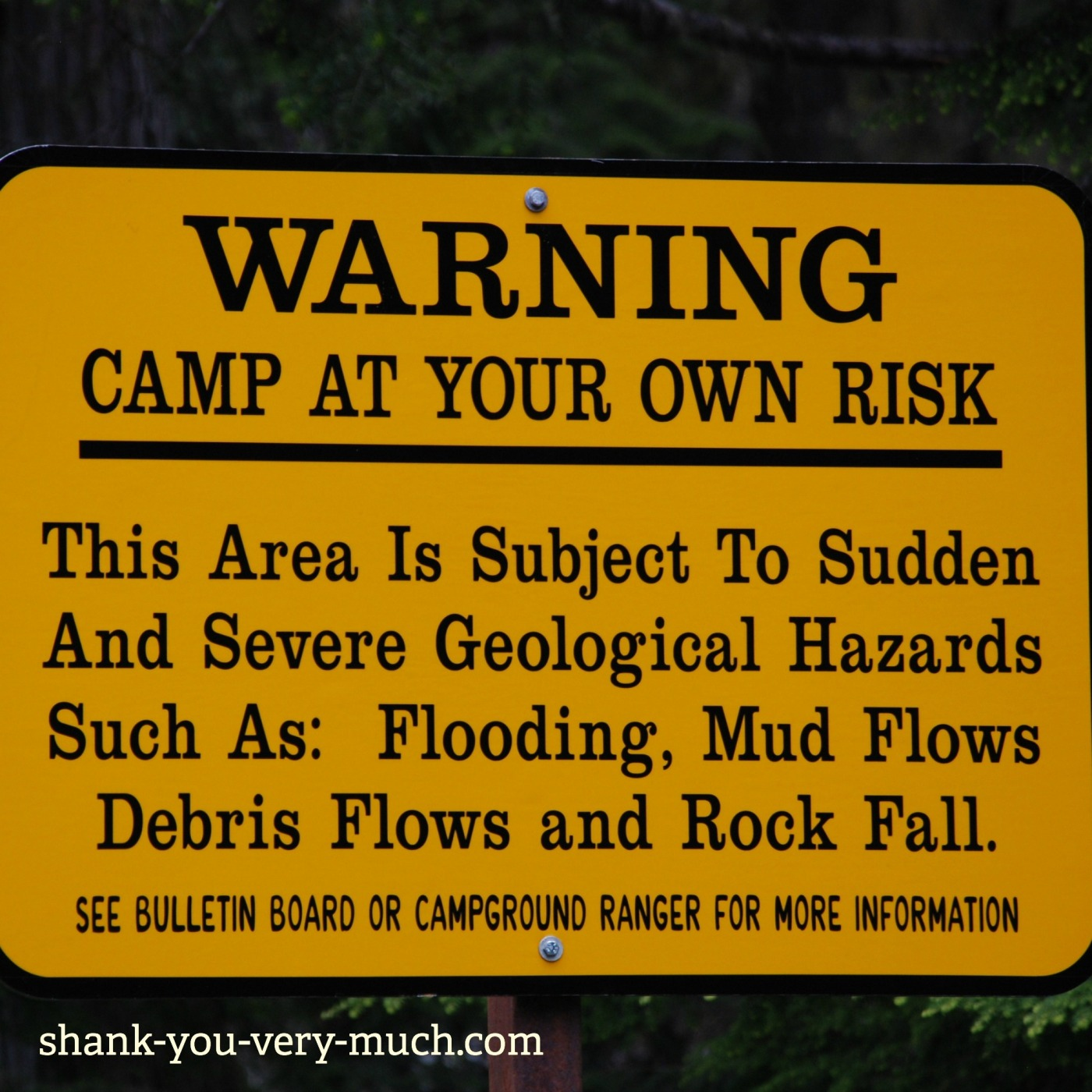 """A warning sign that says """" Camp at your own risk. This area is subject to sudden and severe geological hazards such as: flooding, mud flows, debris flows and rock fall."""""""